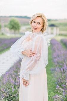 Charmante femme blonde mature sympathique en élégante robe longue beige posant dans un champ de lavande. dame d'âge moyen en robe à l'extérieur.
