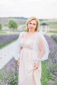 Charmante femme blonde mature sympathique en élégante robe longue beige posant dans un champ de lavande