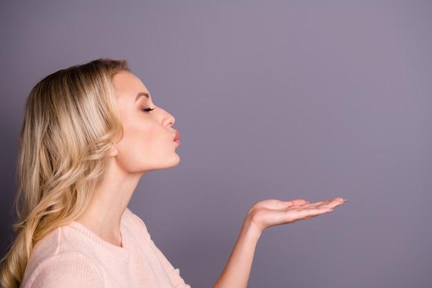 Charmante femme blonde posant contre le mur violet