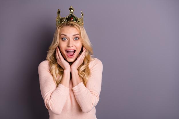 Charmante femme blonde en pull rose posant avec couronne contre le mur violet