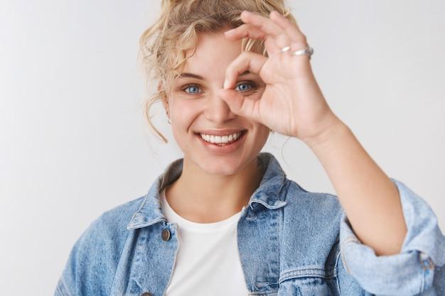 Charmante femme blonde scandinave souriante et souriante, coupe de cheveux bouclée, yeux bleus souriants, spectacle de rêve, ok signe génial, regarde à travers le geste ok souriant ravi, satisfait de bonne qualité