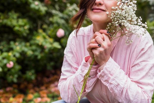 Charmante femme avec bouquet de plantes à fleurs blanches près du visage