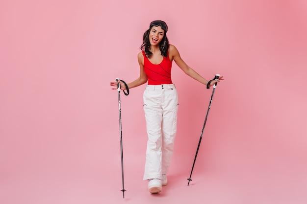 Charmante femme bronzée tenant des bâtons de ski