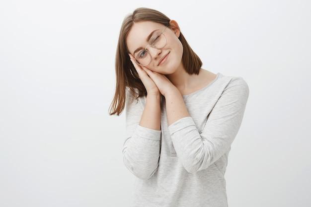 Charmante femme brune caucasienne douce et mignonne aux cheveux bruns courts s'appuyant sur les paumes comme si elle dormait furtivement avec un œil et souriant joyeusement debout dans des verres et chemisier sur un mur gris
