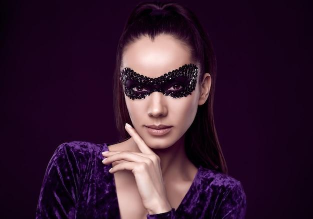 Charmante femme brune élégante en robe violette et masque de paillettes