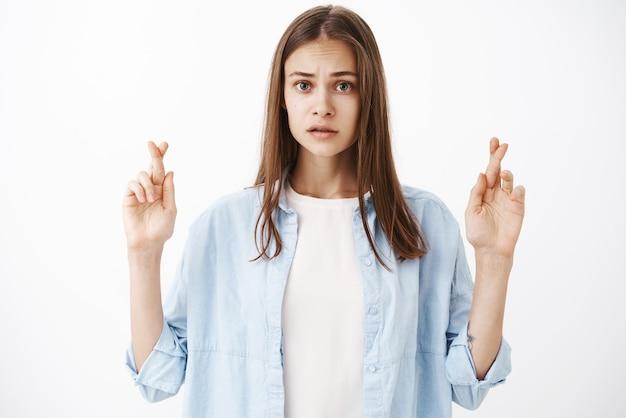 Charmante femme brune inquiète et inquiète avec une coupe de cheveux moyenne fronçant les sourcils à la recherche de doigts croisés nerveux pour avoir de la chance, faire un souhait ou prier en attendant que quelque chose d'important se produise