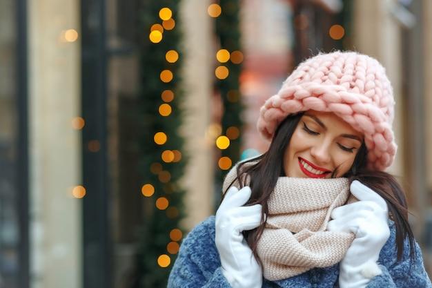 Charmante femme brune en manteau marchant dans la ville en hiver. espace libre