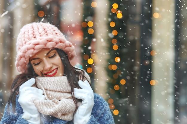 Charmante femme brune en manteau marchant dans la ville pendant les chutes de neige. espace libre