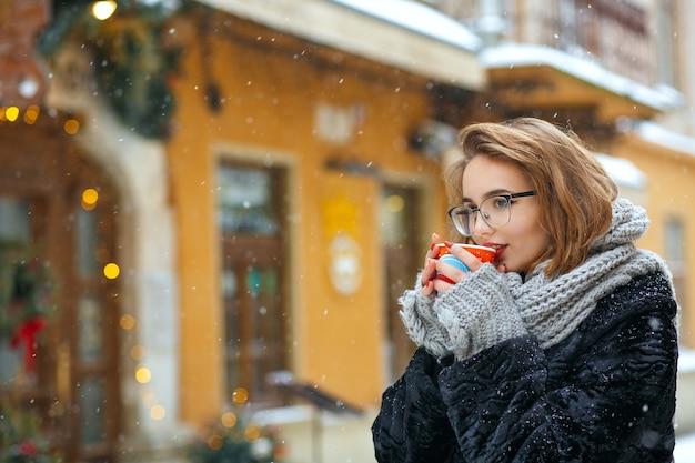 Une charmante femme brune porte une écharpe grise et des lunettes boit du café dans la rue pendant les chutes de neige. espace libre
