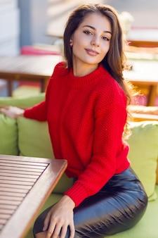 Charmante femme brune en pull tricoté automne rouge et jupe en cuir reposant sur un canapé dans un restaurant en espace ouvert.