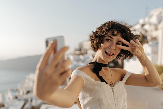 Une charmante femme brune en robe beige montre un signe v, fait une grimace et prend un selfie à l'extérieur sur les murs de la vieille ville