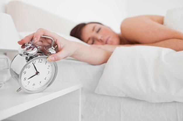 Charmante femme brune se réveiller avec une horloge en position couchée