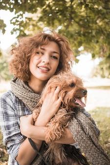 Charmante femme caresser le chien dans le parc