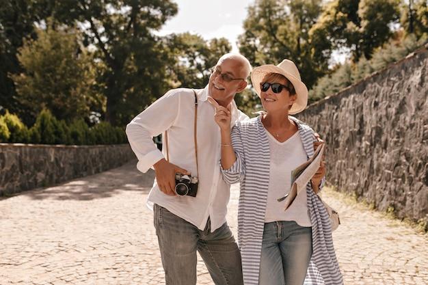 Charmante femme avec une coiffure courte en chapeau et chemisier bleu tient la carte, pointe vers le côté et sourit avec un homme aux cheveux gris avec caméra dans le parc.