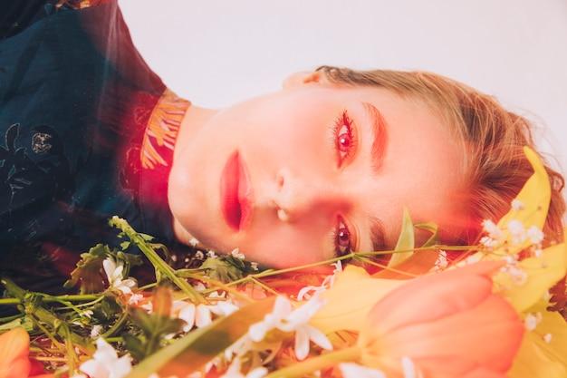 Charmante femme couchée avec bouquet de fleurs en rose