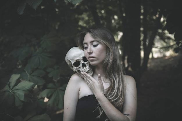 Charmante femme avec un crâne dans un fourré