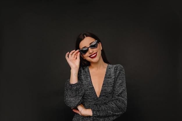 Charmante femme élégante avec des lèvres rouges tenant ses lunettes et ses sourires