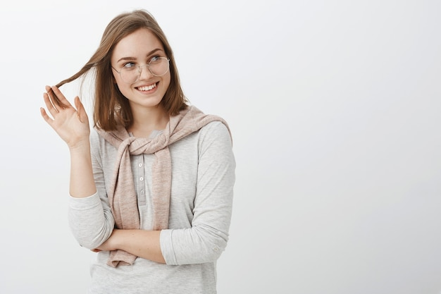 Charmante femme européenne charmante féminine à lunettes et sweat-shirt noué sur le cou jouant avec une mèche de cheveux souriant et regardant à droite avec admiration et désir posant sur un mur blanc