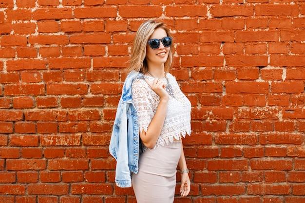 Charmante femme heureuse jeune hipster avec un beau sourire dans un chemisier en dentelle blanche dans une veste en jean à lunettes de soleil noires dans une jupe beige posant près d'un mur de briques rouges