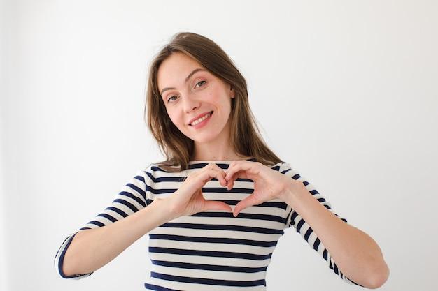 Charmante femme montrant le geste du coeur