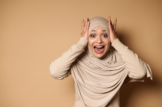 Une charmante femme musulmane en hijab et vêtements stricts tient sa tête à deux mains et regarde la caméra avec surprise.