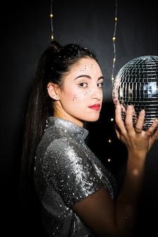 Charmante femme avec des paillettes sur le visage tenant une boule disco