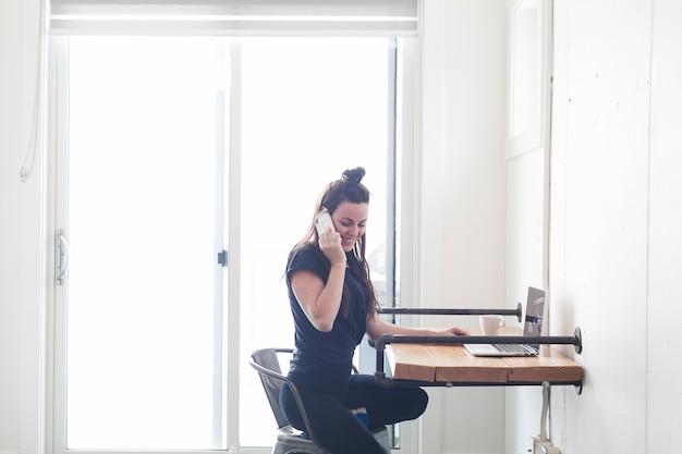 Charmante femme parlant au téléphone à table