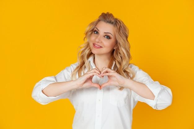 Charmante femme passionnée blonde charismatique romantique aux yeux bleus montre un geste de reconnaissance du coeur sympathie sympathique
