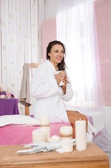 Charmante femme en peignoir blanc relaxant sur un décor de salon de beauté