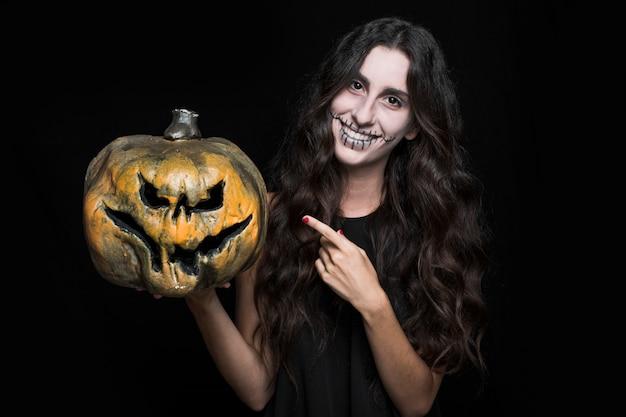 Charmante femme pointant la citrouille d'halloween