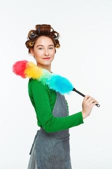 Charmante femme posant en travaillant avec plumeau dans les mains