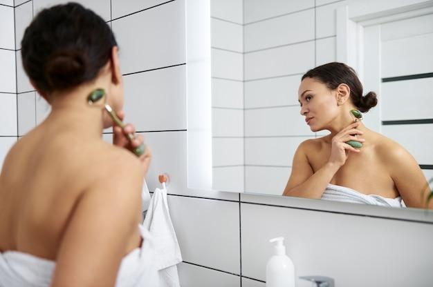 Charmante femme prenant soin de la peau avec rouleau facial de jade.jeune femme massant son cou avec un outil de massage