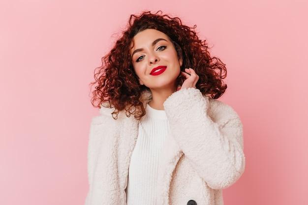 Charmante femme en pull blanc élégant et manteau de fourrure sourires mignons. portrait de femme bouclée aux yeux bleus et aux lèvres rouges.