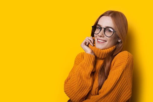 Charmante femme de race blanche portant un pull jaune chaud pose sur un mur avec un espace libre portant des lunettes