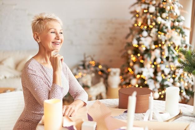 Charmante femme retraitée émotionnelle avec une coiffure de lutin, profitant des préparations de noël, emballant des cadeaux dans du papier kraft, ayant une expression faciale joyeuse, faisant des cadeaux pour la famille et les amis