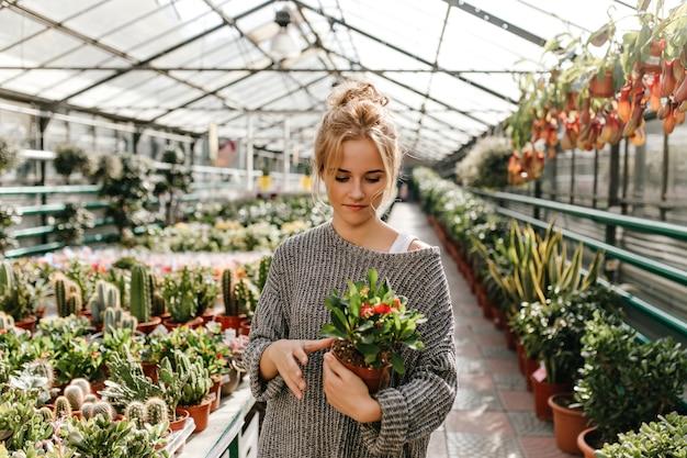 Charmante femme en robe tricotée tenant un pot avec fleur. femme marche le long de l'allée de la serre.
