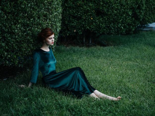 Charmante femme en robe verte est assise sur la pelouse de brousse verte de luxe.