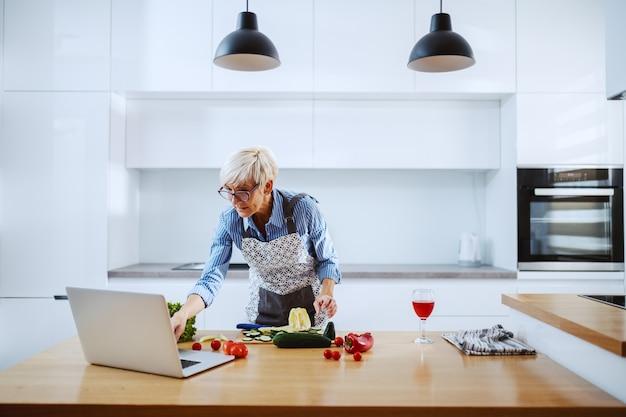 Charmante femme senior blonde en tablier et avec des lunettes debout dans la cuisine, à l'aide d'un ordinateur portable et de préparer un repas sain