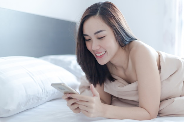Charmante femme sexy joue sur téléphone portable sur le lit