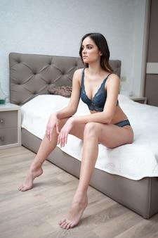 Charmante femme sexy en lingerie allongée sur le lit dans la chambre