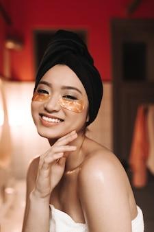 Charmante femme avec un sourire blanc comme neige regarde à l'avant