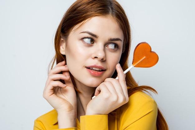 Charmante femme avec sucette dans les mains look attrayant studio fond isolé. photo de haute qualité