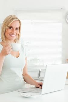 Charmante femme avec une tasse de café et un ordinateur portable regardant dans la caméra