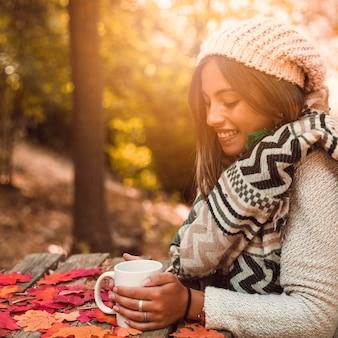 Charmante femme avec une tasse une table en automne parc