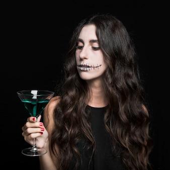 Charmante femme tenant gobelet de liquide turquoise