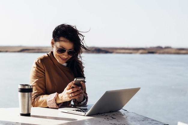 Charmante femme travaillant à l'extérieur, tapant un message sur son mobile