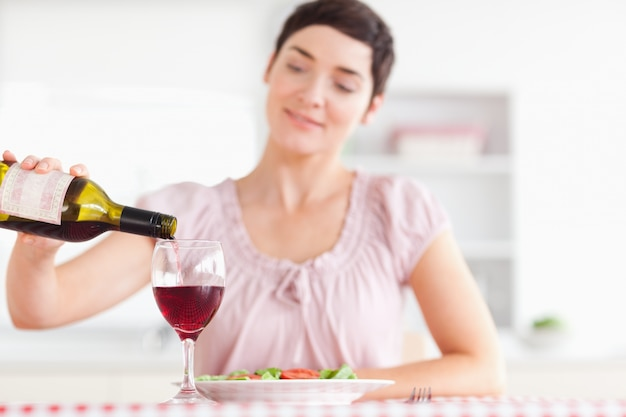 Charmante femme versant le vin rouge dans un verre