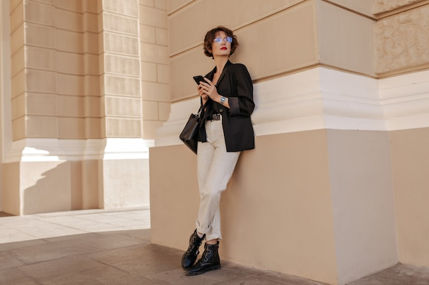 Charmante femme en veste et pantalon léger tenant le téléphone à l'extérieur. femme aux cheveux courts à lunettes avec sac à main noir posant à l'extérieur.
