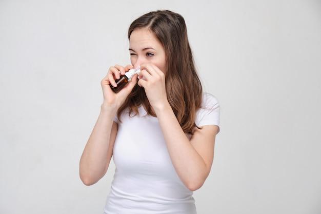 Charmante femme vêtue d'un t-shirt blanc, squissing médecine dans le nez. concept de prévention et de traitement du rhume et de la grippe.
