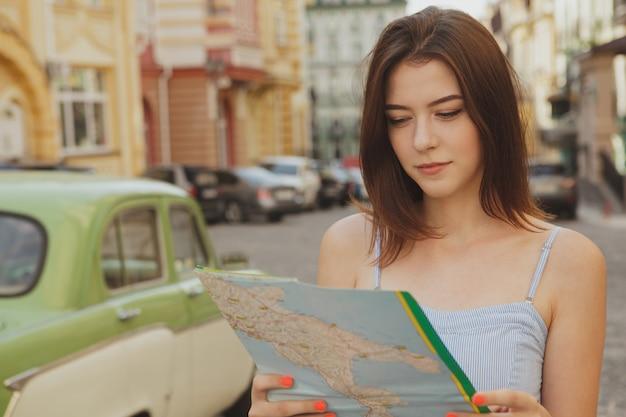 Charmante femme visite en utilisant une carte, espace de copie